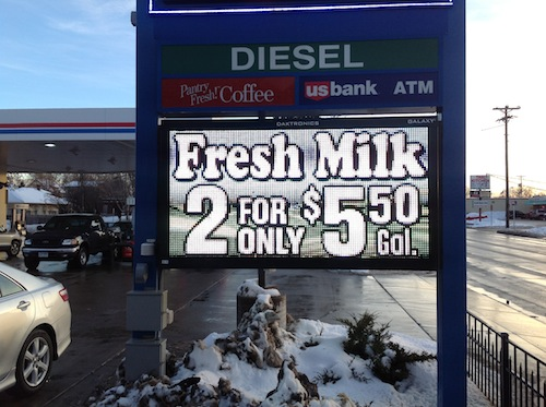 Sign in front of gas station advertising milk prices